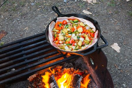 Cooking dinner over fire in cast iron skillet bacon veggie stir fry