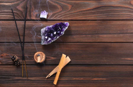Composition of esoteric objects used for healing, meditation, relaxation and purifying. Amethyst stones, palo santo wood, Aromatic scent sticks on  dark wood background.