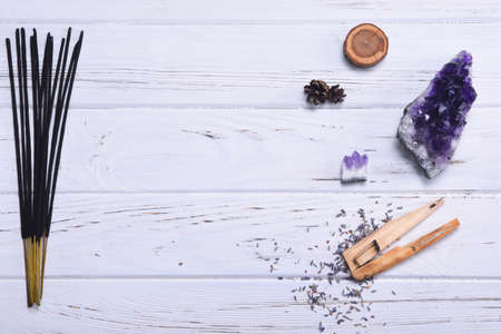 Composition of esoteric objects used for healing, meditation, relaxation and purifying. Amethyst stones, palo santo wood, Aromatic scent sticks on white background. 免版税图像