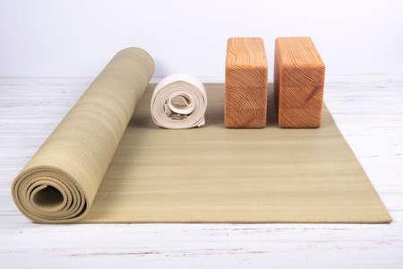 Grüne Yogamatte, zwei Holzklötze und weißer Gürtel auf weißem hölzernem Hintergrund mit Kopienraum. Yoga-Praxis, Entspannung und Meditationskonzept