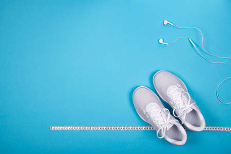 Top view of white sport shoes (sneakers) with measuring tape and white earphones (headphones) on cyan blue background. Losing weight and sport concept. Flat Lay. Foto de archivo