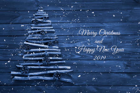 View from above of Christmas tree made of dry wooden branches with pine cones decoration on wooden table background, blue color. New Year and Christmas card.