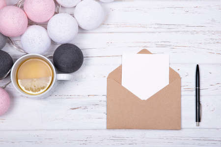 Composition of single cup of tea with lemon, white blank card in opened craft envelope and black pen, decorated with different colors cotton balls light garland on white planked wooden background with copy space. Creativity concept. Flat lay. Top view.