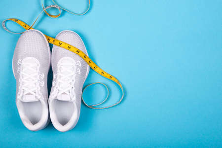 Top view of white sport shoes (sneakers) with yellow measuring decimeter tape on cyan blue background. Losing weight and sport concept with copy space. Flat Lay.