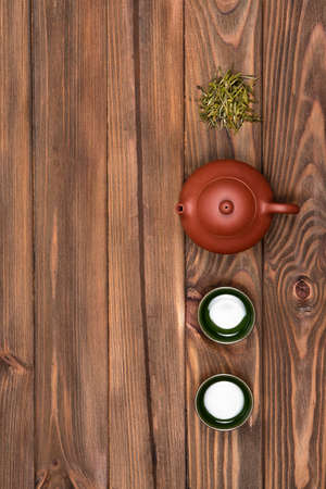Top view of brown ceramic teapot, two dark green small special cups and green tea on a dark wooden planked background. Tea ceremony. Flat lay.