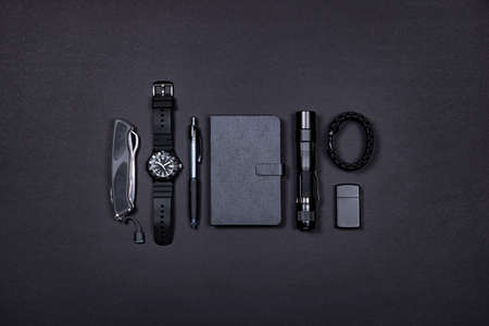 Top view of everyday carry (EDC) items for men in black color - folding knife, lighter, note book, tactical pen, watch, survival bracelet and flashight. Minimal concept. Survival set.