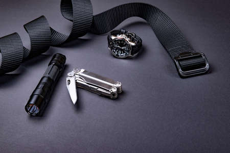 Everyday carry (EDC) items for men in black color - tactical belt, flashlight,  watch and silver multi tool. Survival set. Minimal concept. 版權商用圖片