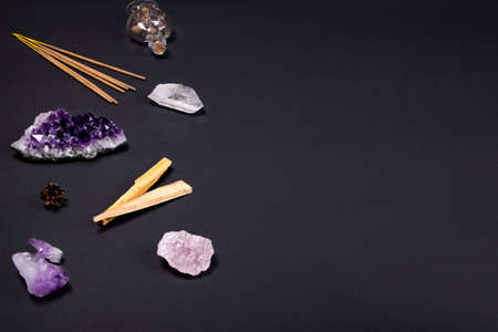 Composition of esoteric objects used for healing, meditation, relaxation and purifying. Amethyst and quartz crystal stones, palo santo wood, aromatic sticks, cone and decorative bottle on dark black background. Copy space.