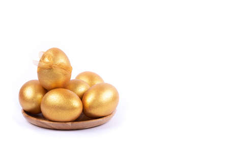 Six golden colored and decorated with bow Easter eggs on wooden plate isolated on white background. Happy Easter greeting card. Copy space. Easter background.