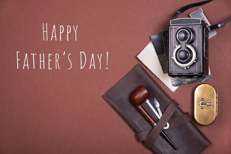 Happy Father's day greeting card with composition of smoking pipe on a brown leather case, tobacco box and tamper, old camera and vintage photographs on dark background with inscription Happy Father's day. Top view.