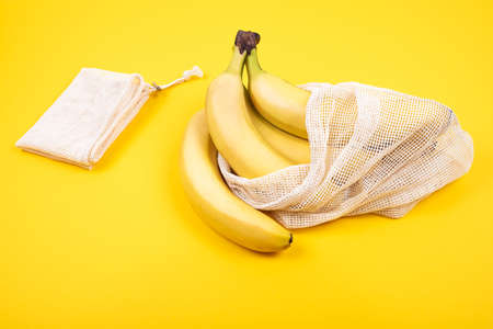 Bunch of fresh bananas in plastic free recycled textile bag for fruits and vegetables on yellow background. Eco concept. Zero waste lifestyle.  Copy space. Imagens