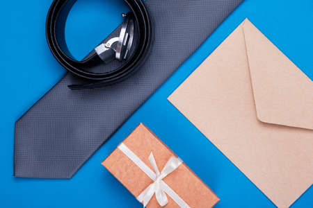 Composition of man's accessories grey (silver) neck tie, gift box, brown craft paper envelope and belt on blue cyan background. Top view. Man's fashionable style concept.