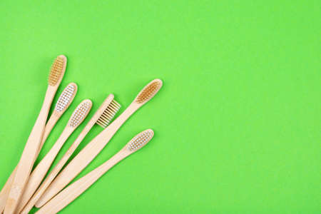 Top view of bamboo toothbrushes on green background. Flat Lay. Zero waste eco life concept. Plastic free. Place for text.