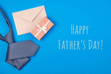Happy Father's day greeting card with composition of grey silver neck tie, gift box with white ribbon and brown craft paper envelope on blue cyan background with inscription Happy Father's day. Top view. Man's fashionable style concept.