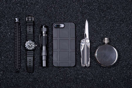 Top view of everyday carry (EDC) items for men in black color - multi tool, lighter, mobile phone in protect case, tactical watch, paracord survival bracelet,flashlight and flask black stone (minerals) crumb background. Flat lay. Minimal concept. Survival military set.