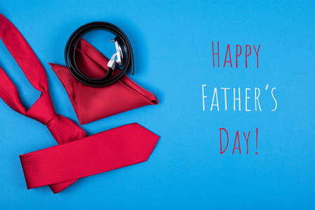 Happy Father's day greeting card with composition of man�¢s accessories red neck tie, pocket square and belt on blue cyan background with inscription Happy Father's day. Top view. Man's fashionable style concept. Stockfoto