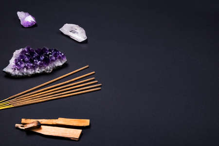 Composition of esoteric objects used for healing, meditation, relaxation and purifying. Amethyst and quartz crystal stones, palo santo wood, Aromatic sticks on dark black background. Copy space.