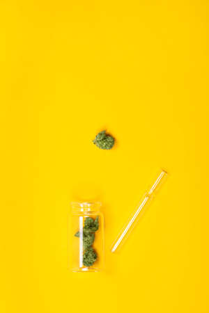 Dried medical marijuana buds in a small open glass jar and scattered aside and pipe on yellow background. Alternative treatment. Medical cannabis. Copy space. 免版税图像