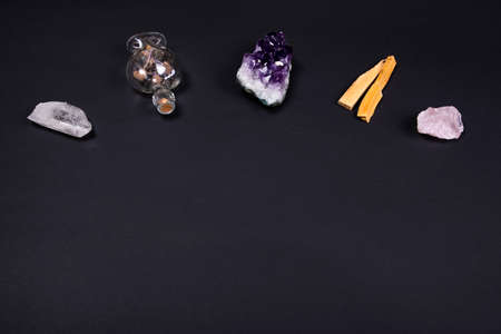 Composition of esoteric objects used for healing, meditation, relaxation and purifying. Amethyst and quartz crystal stones, palo santo wood and decorative bottle on dark black background. Copy space.