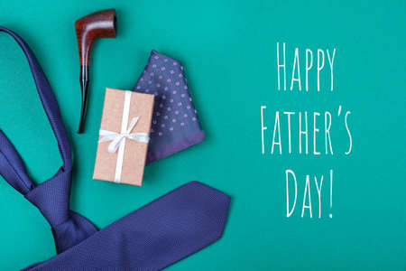 Happy Father's day greeting card with composition of violet dotted neck tie, gift box with white ribbon, pocket square and smoking tobacco pipe on emerald blue-green background with inscription Happy Father's day. Man's fashionable style concept.