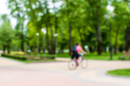 Blurred background with silhouette of a woman rides a bike (cyclist) in th epublic city park on the sidewalk.