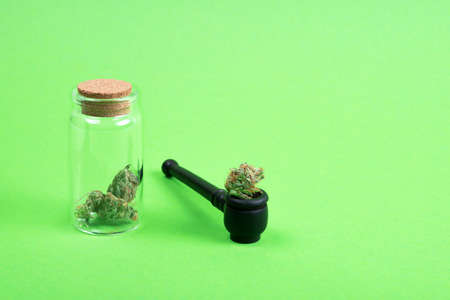 Dried medical marijuana buds in a small open glass jar with wooden pipe on green background. Alternative treatment. Medical cannabis. Place for text.