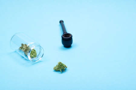 Dry medical marijuana buds in open glass jar and scattered aside and wooden pipe on blue background. Alternative treatment. Medical cannabis.