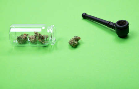 Dried medical marijuana buds in a small open glass jar and scattered aside with wooden pipe on green background. Alternative treatment. Medical cannabis. Copy space.