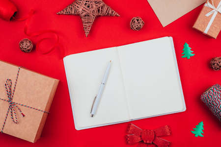 Top view of blank notebook, pen, craft gift boxes, envelope, red bow, clew of tricolor rope, ribbon and decorations over red festive background. Flat lay. Christmas concept. Wish list.