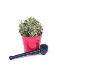 Composition of fresh green buds or flowers of cannabis marijuana weed in small metal decorative red bucket and smoking pipe. Alternative treatment. Medical cannabis. Space for text.