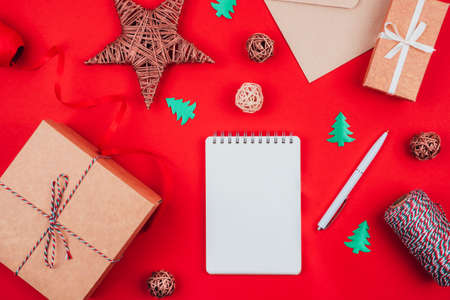 Top view of blank notebook, pen, craft gift boxes, envelope, red bow, clew of tricolor rope, ribbon and decorations over red festive background. Flat lay. Christmas and New Year concept.
