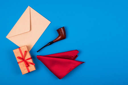 Composition of gift box with bow, red pocket square, smoking tobacco pipe and craft paper envelope on blue background with icopy space. Space for text. Top view. Mans fashionable style concept.