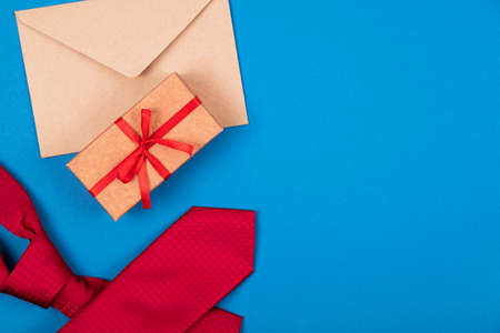 Composition of red neck tie, gift box with ribbon and bow, brown craft paper envelope on blue cyan background. Top view. Mans fashionable style concept. Gift for men.