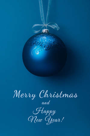 Single Christmas ball with ornament hanging on a ribbon over blue background. Christmas and New Year winter holidays greeting card. Minimal concept. Place for text.