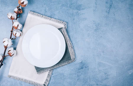 Top view of empty circle plate on linen napkins decorated with cotton flowers on blue grey background.