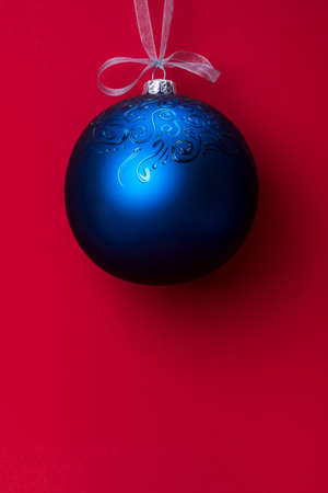 Single Christmas ball with ornament hanging on a ribbon over red background. Christmas and New Year winter holidays greeting card. Minimal concept. Place for text. Stock Photo