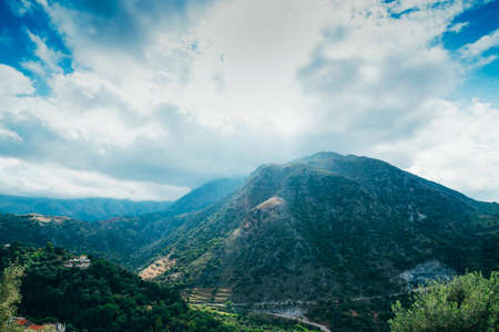 Picturesque landscape with mountains, cloudy sky and green valley in Argiroupolis small village on island Crete, Greece.
