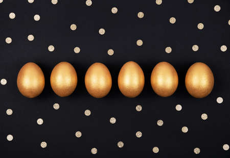 Top view of golden colored Easter eggs in a row and confetti on dark black background. Happy Easter greeting card. Easter background. Place for text.