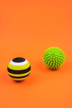 Set of two green myofascial release and massage balls for trigger points over burnt orange color background. Self body care massage and stress, pain relief concept.