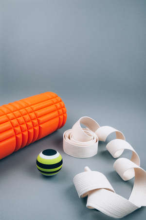 Set of green myofascial release and massage ball, orange bumpy foam massage roller for trigger points and white belt over grey background. Self body care massage and stress, pain relief.