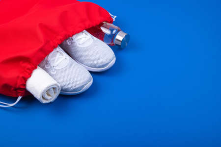 Top view of white sport shoes sneakers, reusable glass water bottle and towel in red sport bag on classic blue background. Set for runners. Losing weight and sport fitness concept. Flat Lay.