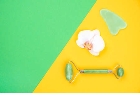 Top view of green face roller and gua sha massager made from natural jade nephritis stone with orchid flower over green and yellow background. Facial massage concept.