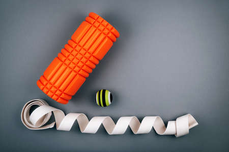 Set of green myofascial release and massage ball, orange bumpy foam massage roller for trigger points and white belt over grey background. Self body care massage and stress, pain relief. Sport concept