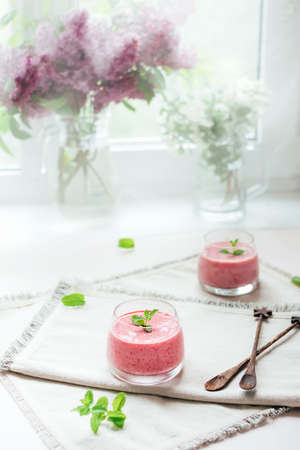 Two glasses of homemade berry smoothie decorated with mint leaves over white napkins in the kitchen. Healthy lifestyle.