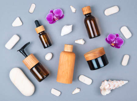 Top view of wooden and glass bottles containers blank mockup for skincare products on grey background with seashells and stones. Zero waste and eco-conscious life beauty spa concept. Flat lay.