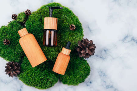 Wooden and glass bottles containers blank mockup for skincare products on natural dark green moss over marble background. Zero waste and eco-conscious life beauty spa concept. Flat lay. Copy space.