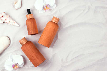 Top view of wooden and glass bottles containers blank mockup for skincare products on white sand background decorated with seashells and stones. Zero waste and eco-conscious life beauty spa concept.