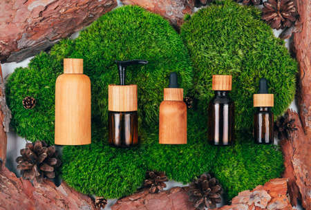 Wooden and glass bottles containers blank mockup for skincare products on natural dark green moss and bark over marble background. Zero waste and eco-conscious life beauty spa concept. Flat lay.