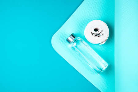 Top view of turquoise yoga mat, white belt and reusable glass water bottle on blue green background. Yoga pilates or fitness practice. Losing weight and sport concept. Flat Lay. Copy space. Stock fotó