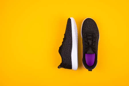 Top view of black sport shoes sneakers on yellow background. Losing weight and sport concept. Flat Lay.Copy space. Stock fotó